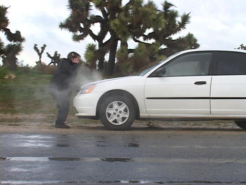 A woman raises the hood of her overheating car Footage