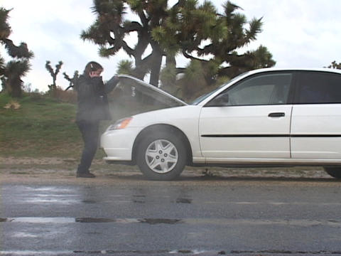 A woman raises the hood of her overheating car Stock Video Footage