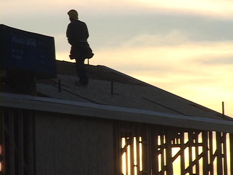A construction worker balances on a roof Stock Video Footage