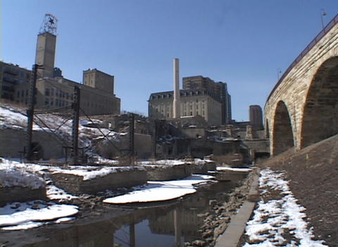 A look at an urban canal in winter with old factories in the background Footage