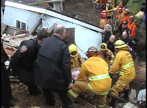 Emergency personnel gently pass a stretcher down a hill Footage