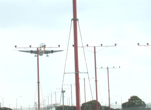 A jet flies low over a group of tall posts Stock Video Footage