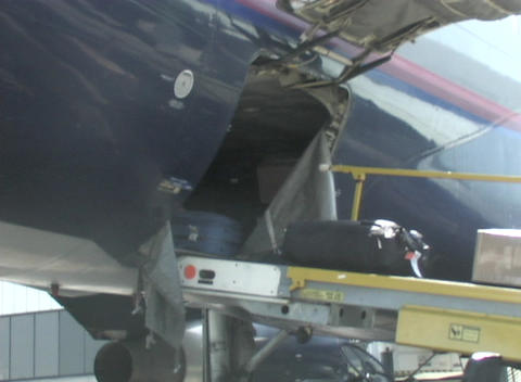 An airline worker unloads baggage from the belly of a... Stock Video Footage