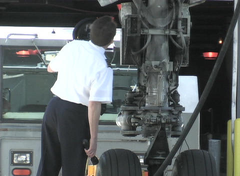 An airline official checks the landing gear of a plane Footage