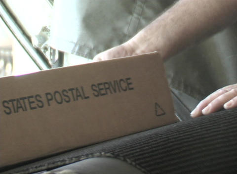 Postal service boxes travel up a conveyor belt into a plane's cargo hold Footage