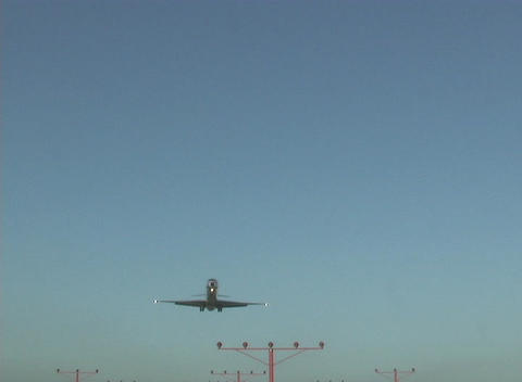 A plane flies over the marker lights on a landing strip Footage