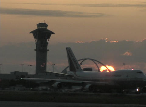 Airplanes taxi at an airport during the golden hour Stock Video Footage