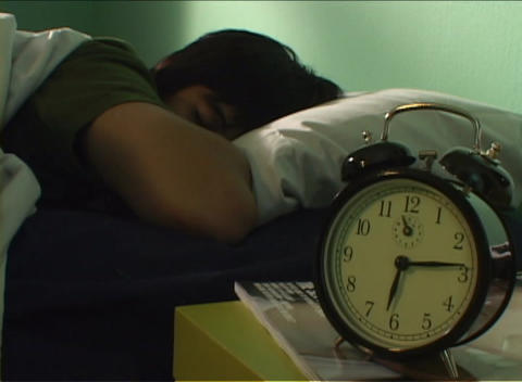 Thirty-minute time-lapse of person trying to stay asleep as clock on bedside table ticks away Footage