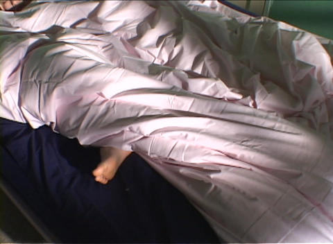 A woman sleeps wrapped in a comforter with her foot... Stock Video Footage