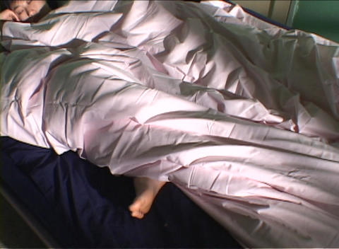 A woman sleeps wrapped in a comforter with her foot dangling outside the covers Footage