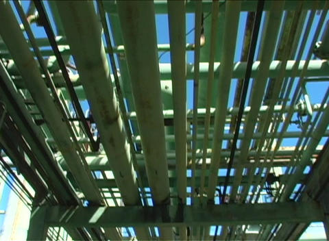 The camera pans the underneath of a large construction made of green pipes Footage