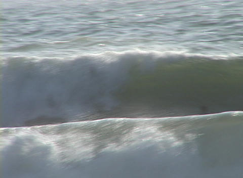 A young man carves through the waves as he surfs in the... Stock Video Footage