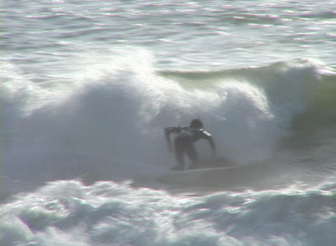 A young man carves through the waves as he surfs in the ocean Footage