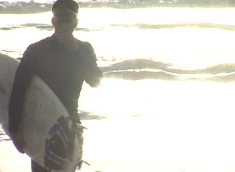 A surfer walks away from the ocean carrying his surf-board at golden-hour Footage