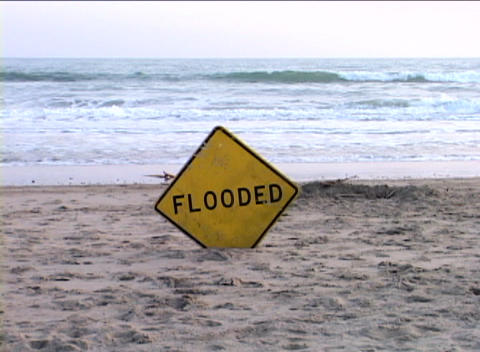 A street sign that reads FLOODED is stuck in the sand on a dry part of a beach with the ocean behind Footage