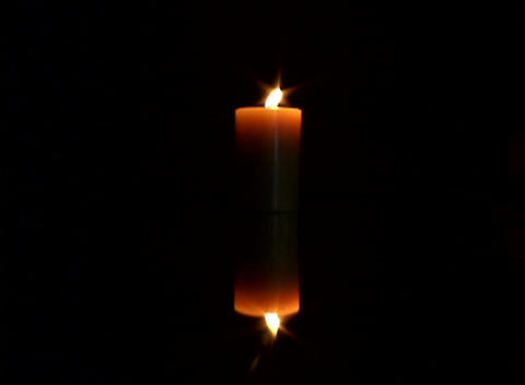 A candle burns in the dark as its reflection is seen... Stock Video Footage