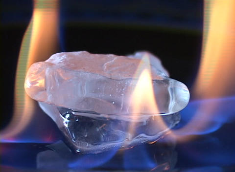 An ice cube is surrounded by flames but isn't melting Stock Video Footage