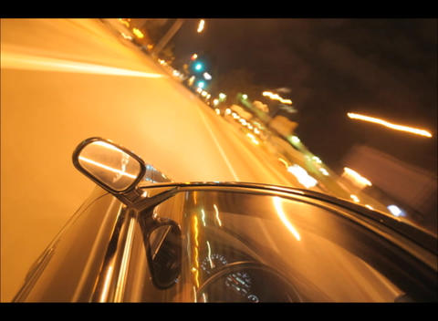 A car speeds through the city streets at night Stock Video Footage