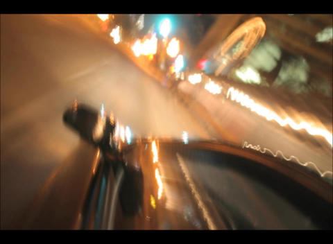 A car speeds through the city streets at night Footage