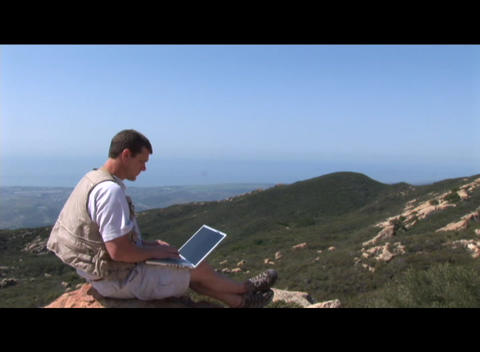 Medium shot of a hiker working on a laptop computer outdoors Footage