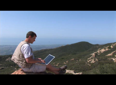 Medium shot of a hiker working on a laptop computer outdoors Stock Video Footage
