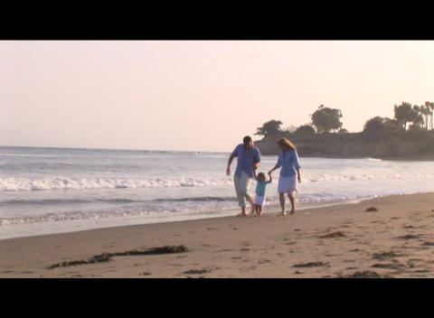 Medium shot of a family strolling on the beach Stock Video Footage