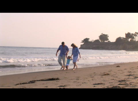 Medium shot of a family strolling on the beach Footage