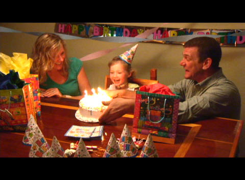 Medium shot of a girl blowing out the candles on her birthday cake Footage