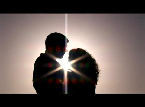 Medium shot of a couple embracing and kissing silhouetted... Stock Video Footage
