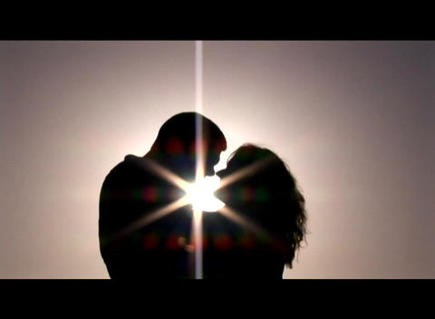 Medium shot of a couple embracing and kissing silhouetted against the sun Footage