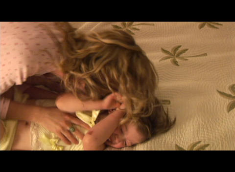 Medium shot of a mother tickling and nuzzling her daughter Footage