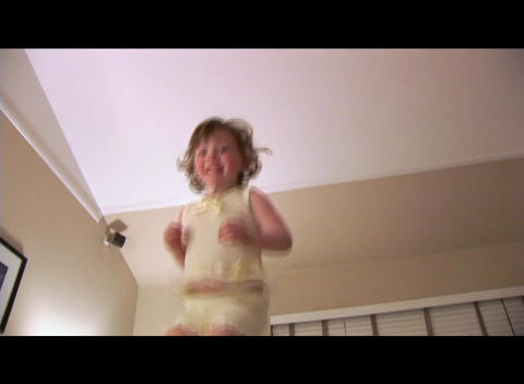 Medium shot of a little girl jump on a bed Stock Video Footage
