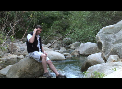 Medium shot of a man talk on a cell phone near a stream Stock Video Footage