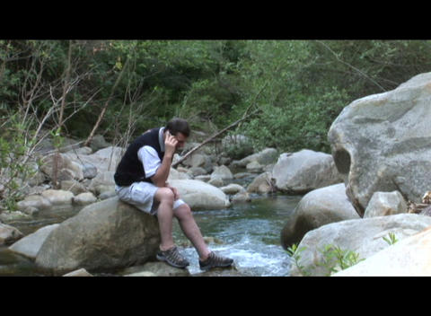 Medium shot of a man talk on a cell phone near a stream Footage