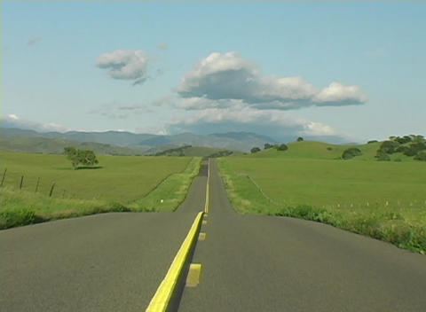 A rural two-lane highway stretches into the distance Footage