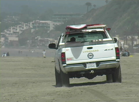 A lifeguard vehicle drives along the sand Footage