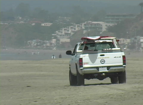 A lifeguard vehicle drives along the sand Stock Video Footage