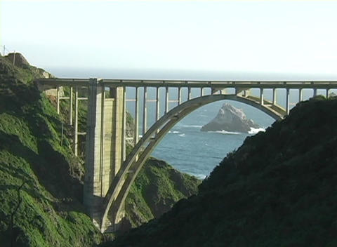 A dramatic traffic bridge connects two hillsides near the coast Footage
