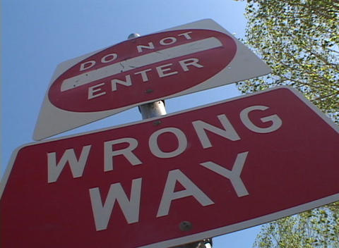 A tilted worm's eye view of a 'Do Not Enter', 'Wrong Way' traffic sign Footage