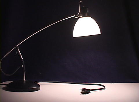 An unplugged desk lamp turns on, illuminating the darkness, then slowly goes out, fading back to bla Footage