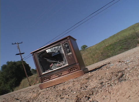 An abandoned vintage television set sits broken, with a shattered screen, on the side of a road Footage