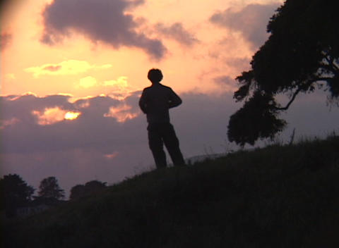 Medium shot of a person standing alone on a hillside... Stock Video Footage