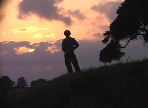 Medium shot of a person standing alone on a hillside during the golden-hour Footage