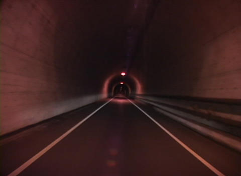 Medium shot traveling through a long tunnel with lights flashing overhead while passing quickly thou Footage