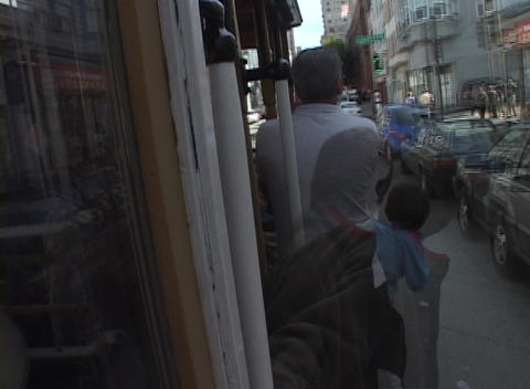 Time-lapse picture of a streetcar traveling down a busy city street with people holding on to the si Footage