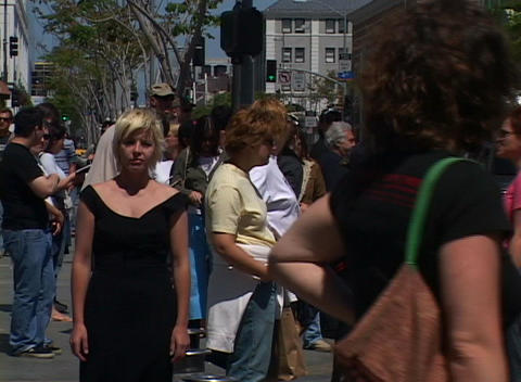 A girl stands motionless and unnoticed on a sidewalk as... Stock Video Footage