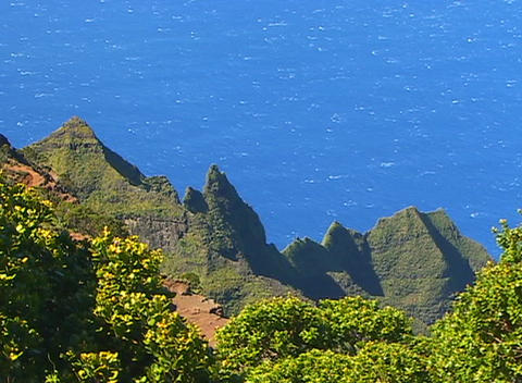 A trail cuts through lush vegetation and triangular volcanic rocks whose profiles tower above the oc Footage