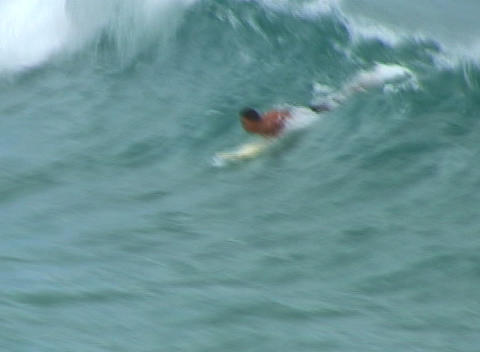 Kneeling on his board, surfer stands to catch a breaking... Stock Video Footage