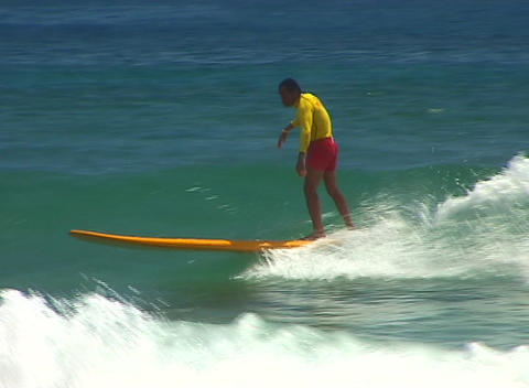 Surfer dressed in bright red and yellow runs out of wave and spills into the foamy water Footage