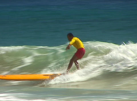 Surfer dressed in bright red and yellow runs out of wave... Stock Video Footage